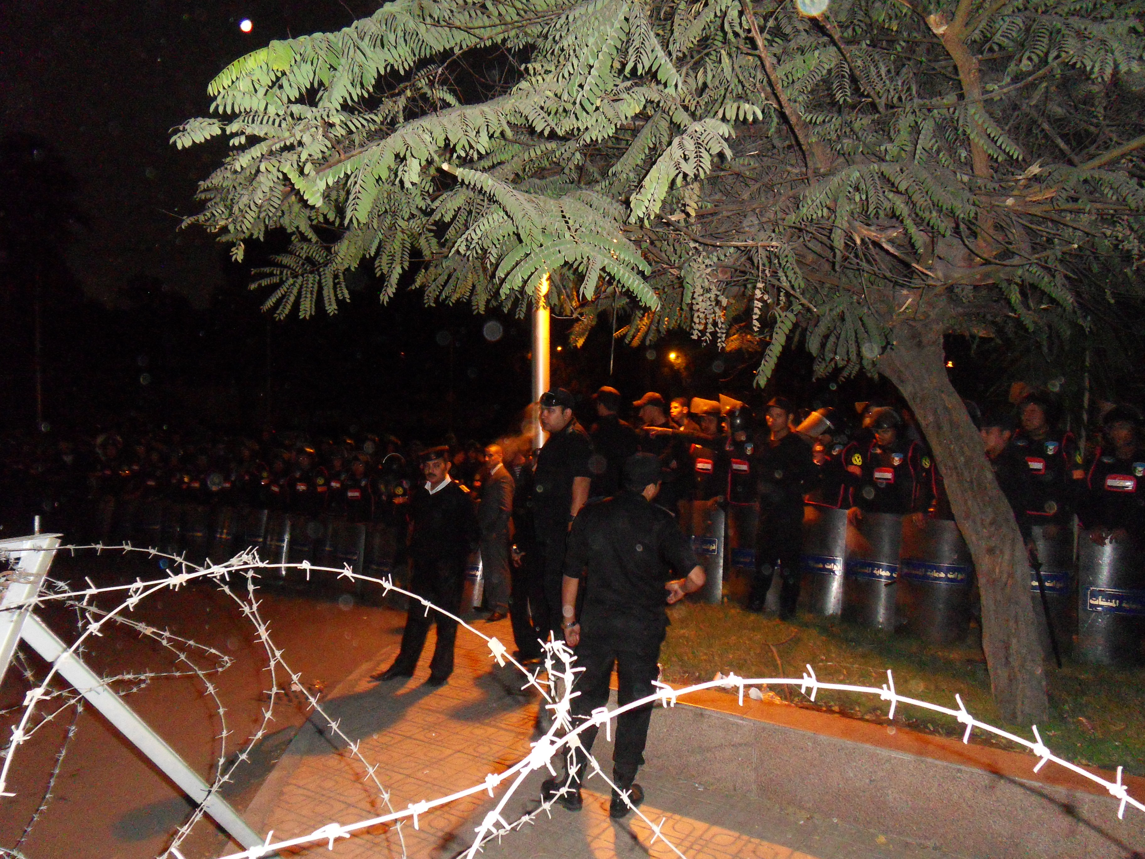 Security Forces blocking the road. People were talking with the officers across the barbed wire.
