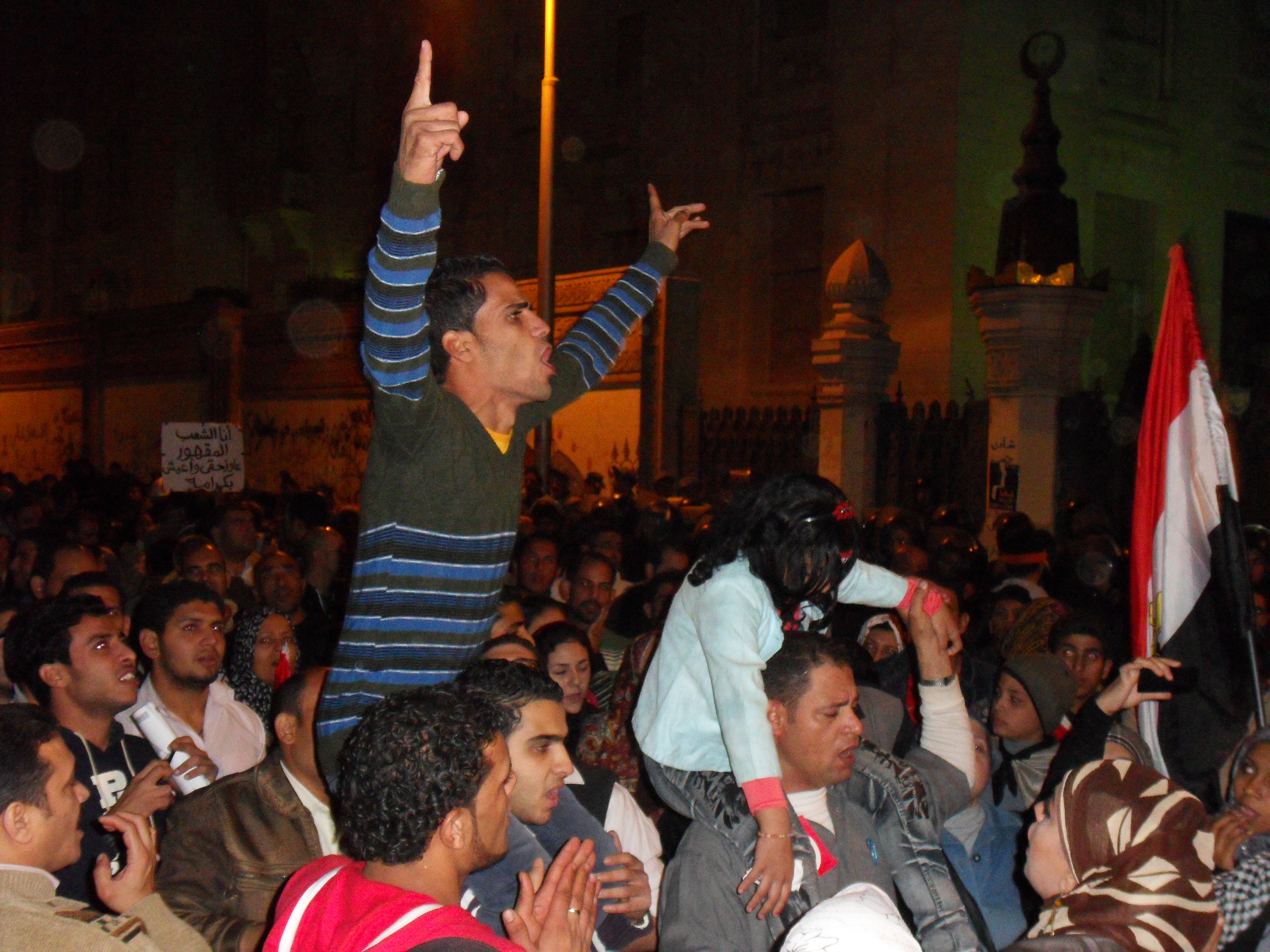 A man riling up the crowd against Morsi in front of the Palace's entrance.