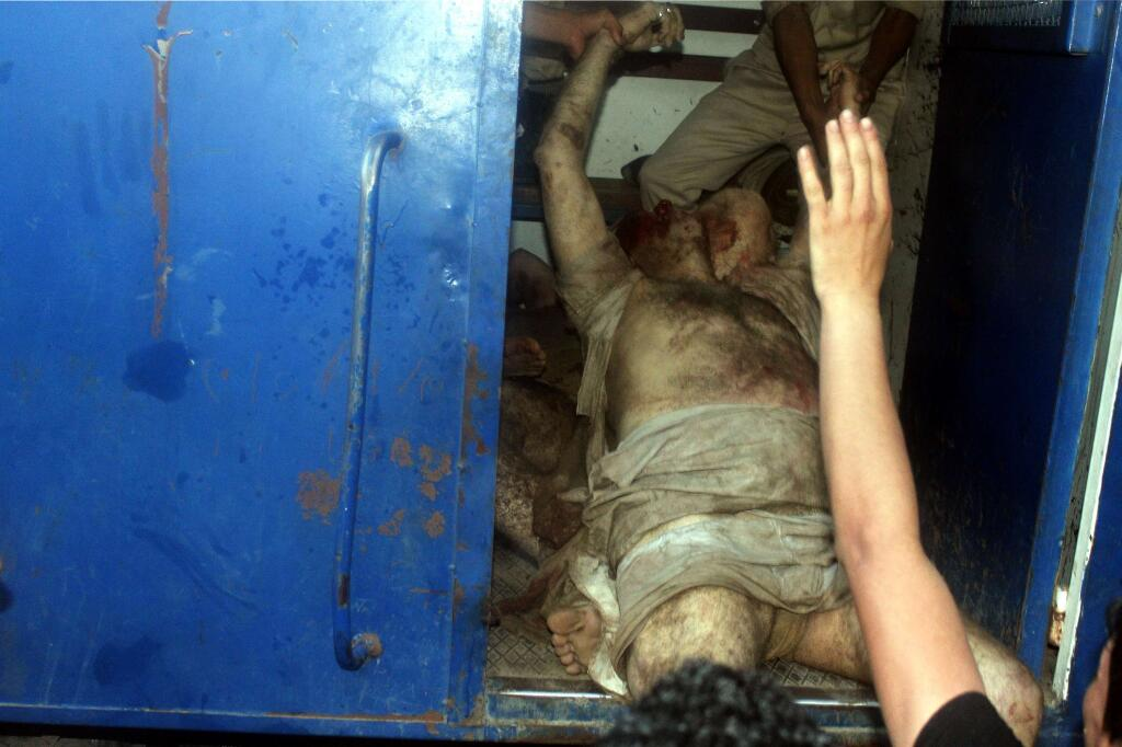 Sheikh Hassan Shehata's lifeless body being pulled into a police van.