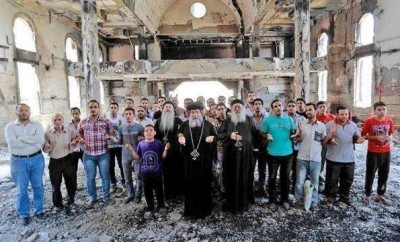 Coptic Christians pray in a burned church in Egypt.