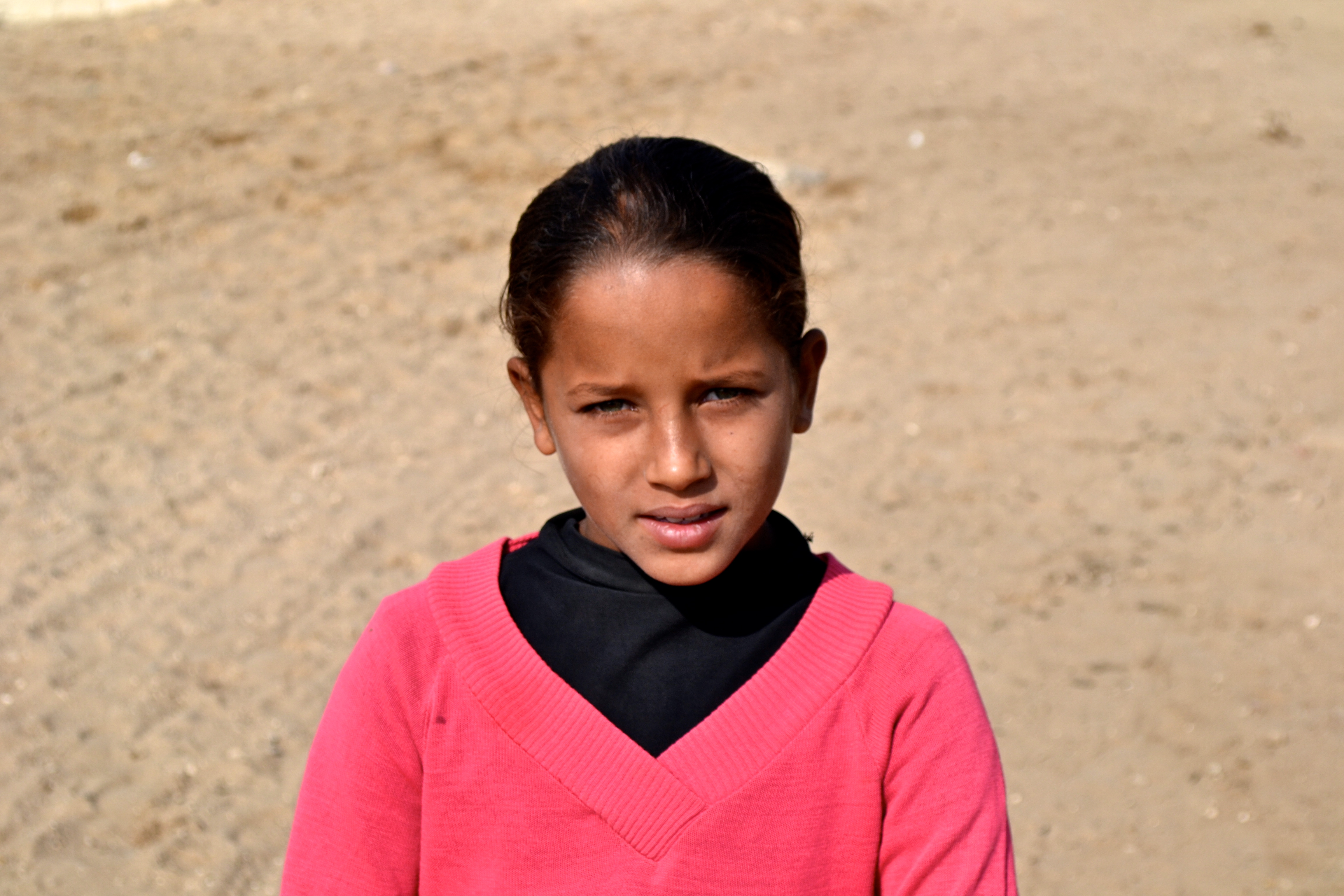 A girl selling souvenirs at the Pyramids to support her family.