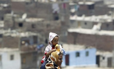 An Egyptian woman carries her child on her shoulders at Manshiyet Nasser shanty town in eastern Cairo