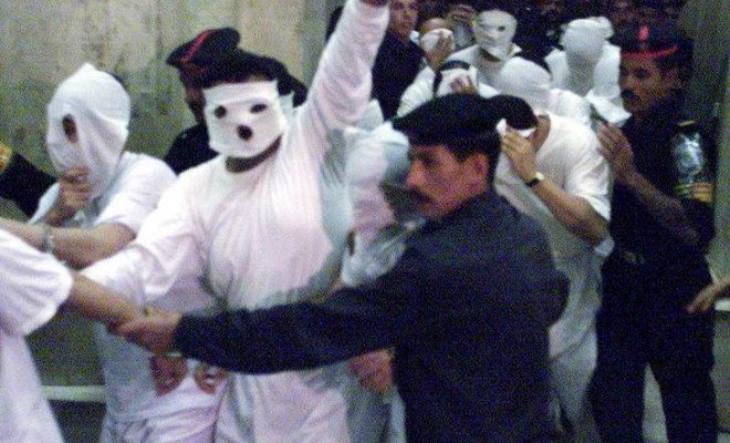 Men accused of homosexual acts hide their faces while attending their trial in 2001