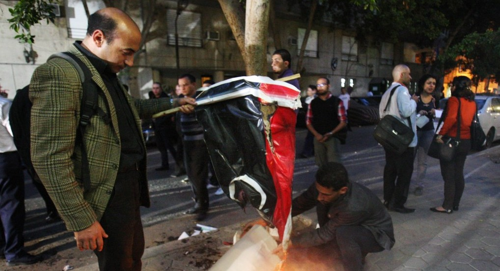Egyptian protesters set fire to the Libyan flag in Cairo in March 2013. Credit: AP
