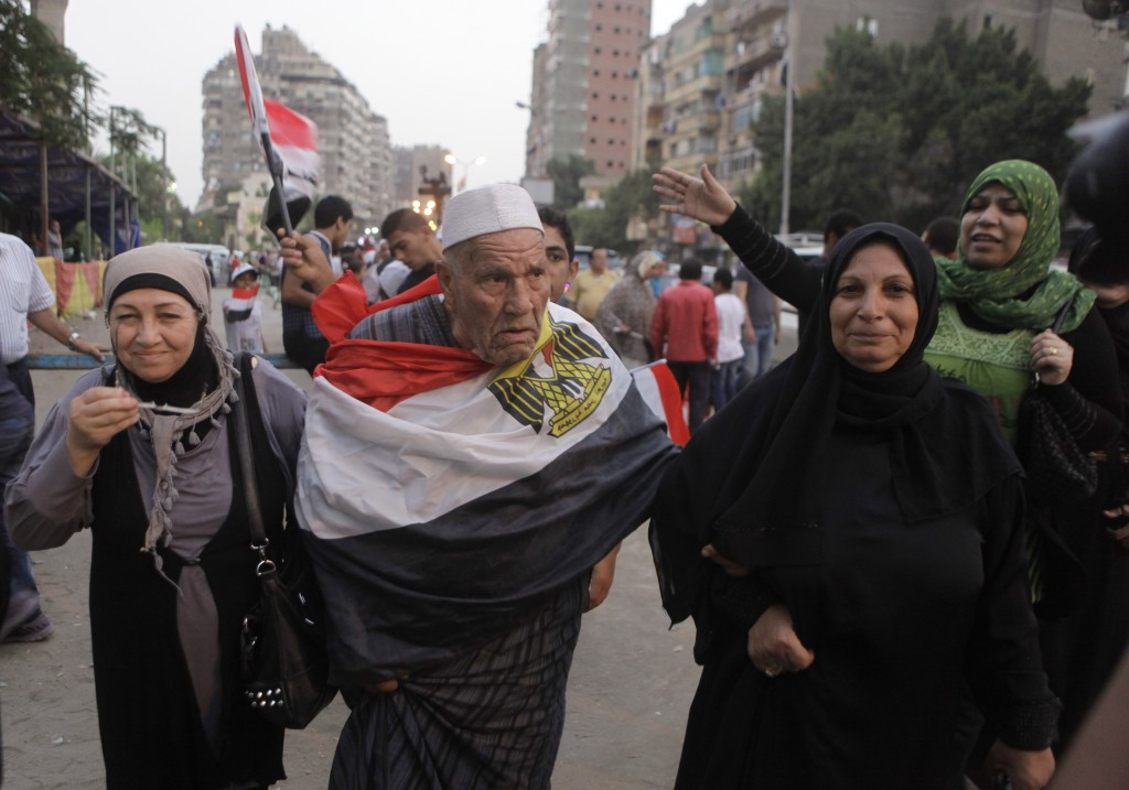 An Egyptian voter heads to the poll with an Egyptian flag wrapped around him. Credit: AP