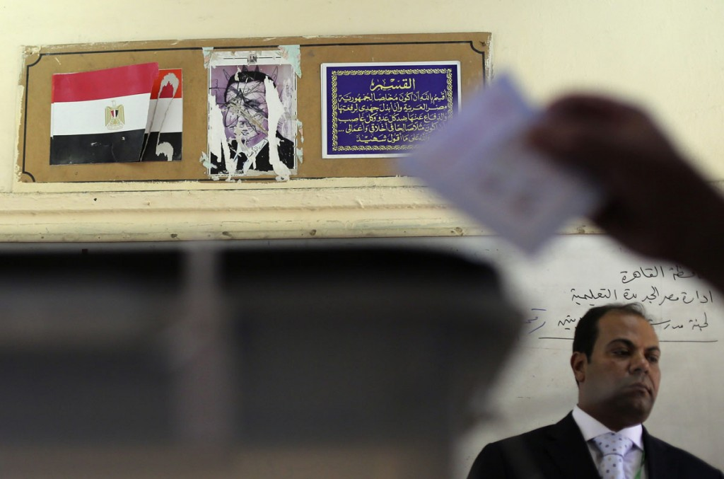 A scratched out photograph of former President Hosni Mubarak hangs at a polling station during the 2014 Presidential elections in Egypt.