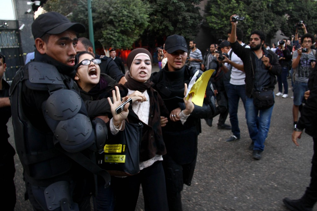 Activist Mona Seif detained by police officers during a protest in November 2013