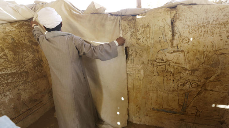 An archaeology worker covers limestones at a newly-discovered tomb in Saqqara. Credit: Amr Nabil/AP