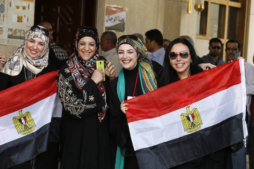 Egyptians holding national flags smile and pose as they arrive to cast their votes for the presidential election at the Egyptian embassy in Riyadh