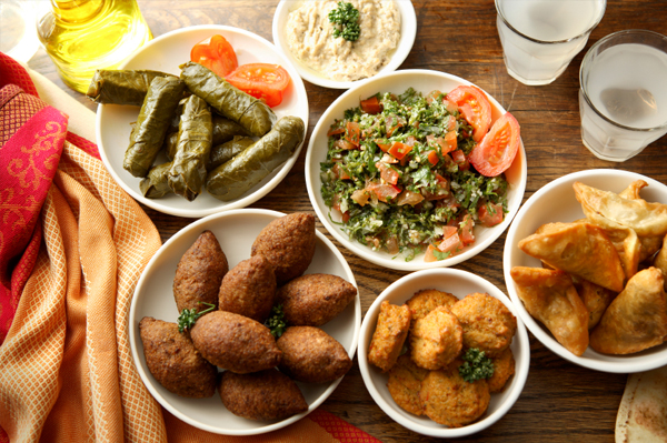 Clock wise: Hummus, Fattoush, Falafel, Kibbeh and stuffed grape leaves.