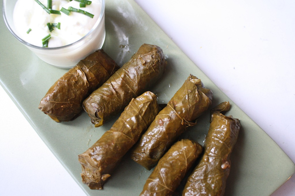 Stuffed grape leaves are often served with a yoghurt salad and lemon.