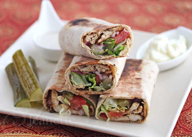 A chicken shawarma wrap served with pickled cucumbers.
