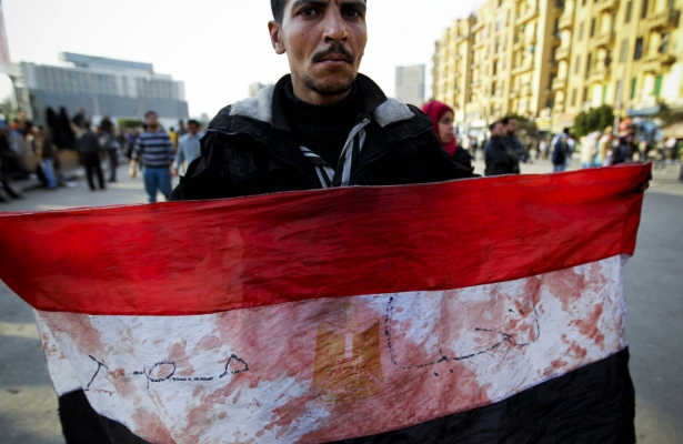 An Egyptian holds a flag spotted with blood during the January 25 revolution in 2011. Credit: AP/Todras-Whitehill