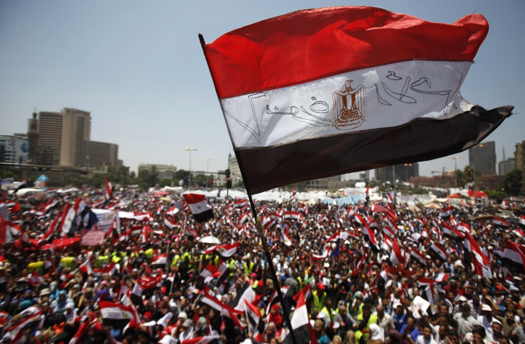 Protesters opposing Egyptian President Mohamed Mursi wave Egyptian flags and shout slogans against him and members of the Muslim Brotherhood at Tahrir square in Cairo