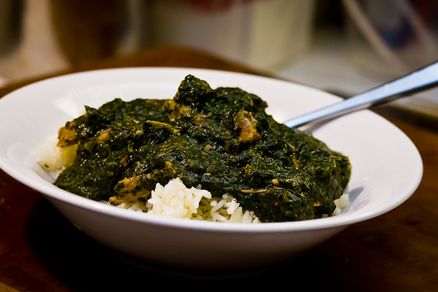 Green leafy mulukhiya soup poured over rice.