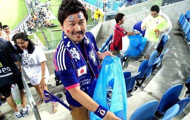 A Japanese fan cleans up after Japan's recent game with Greece.