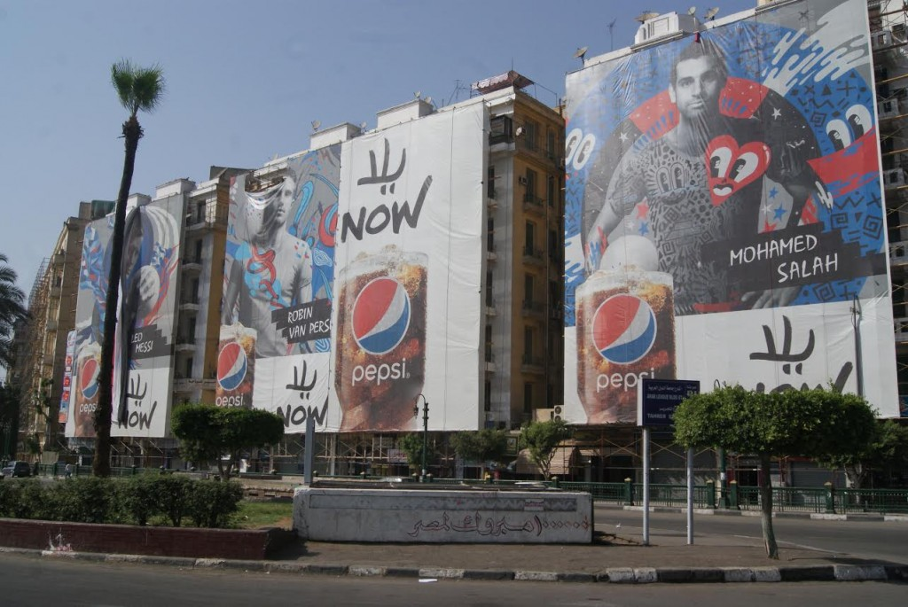 Giant pepsi ads featuring soccer starts cover an entire side of Tahrir square, the heart of the city.
