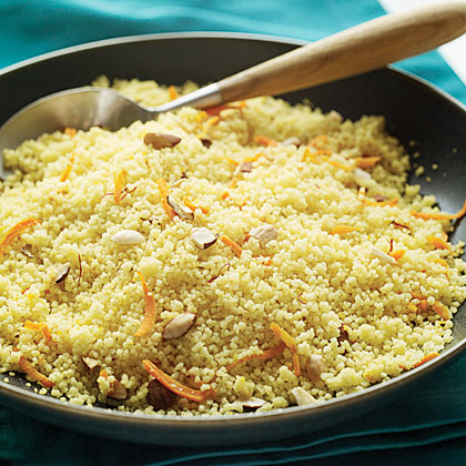 A coucous savory safron dish garnished with nuts and carrots,
