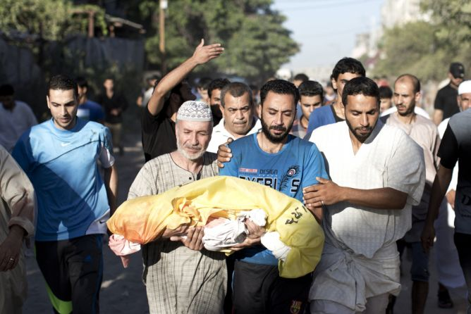 Palestinian mourners carry the body of four-year-old boy Sahir Abu Namus, during his funeral in Jabalia refugee camp in the northern Gaza Strip on July 11, 2014, after he was killed following an Israeli air strike. Israel's aerial bombardment of Gaza claimed its 103rd Palestinian life as Hamas pounded central Israel with rockets and Washington offered to help broker a truce. (MAHMUD HAMS/AFP/Getty Images)