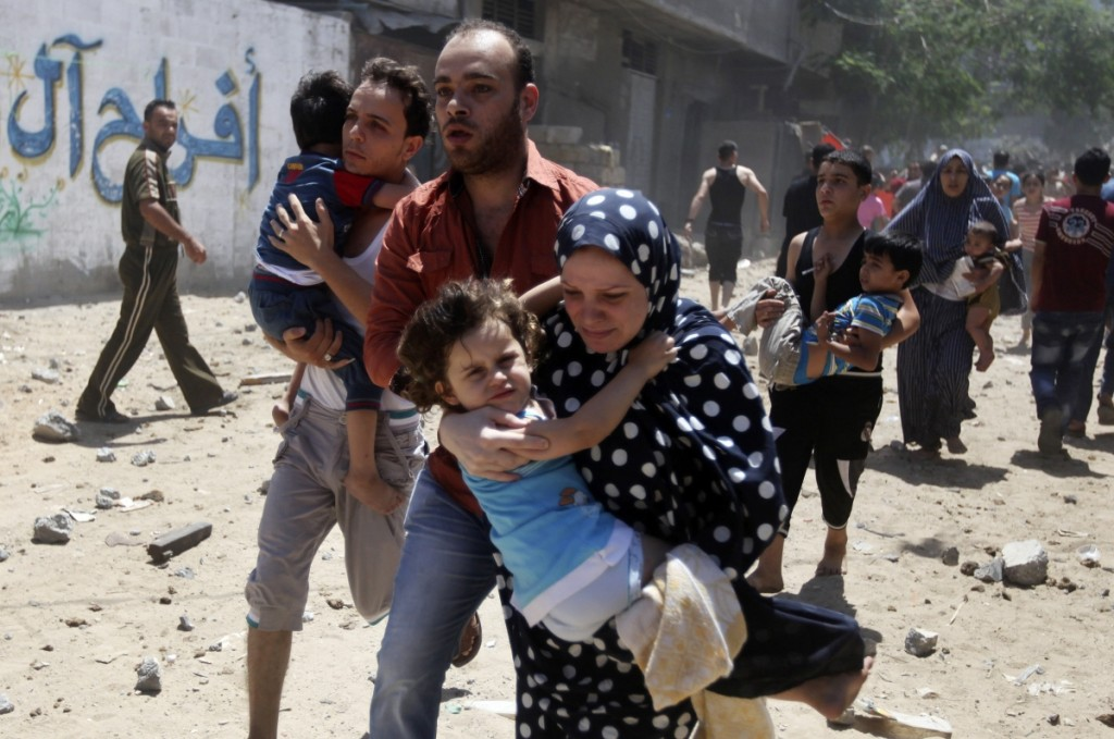 A Palestinian family flees after an air-strike in Gaza. Credit: Reuters