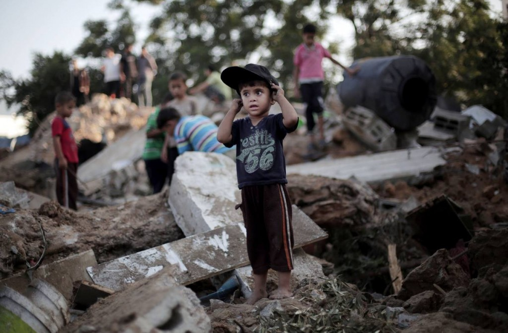 A Palestinian boy plays in the rubble of a destroyed house the day after an Israeli strike in the town of Beit Hanoun, northern Gaza Strip, Wednesday, July 9, 2014. (AP Photo/Khalil Hamra)