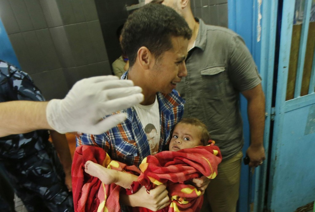 A Palestinian man reacts as he carries a boy, who medics said was wounded in Israeli shelling, at a hospital in Gaza City July 20, 2014. REUTERS/Suhaib Salem