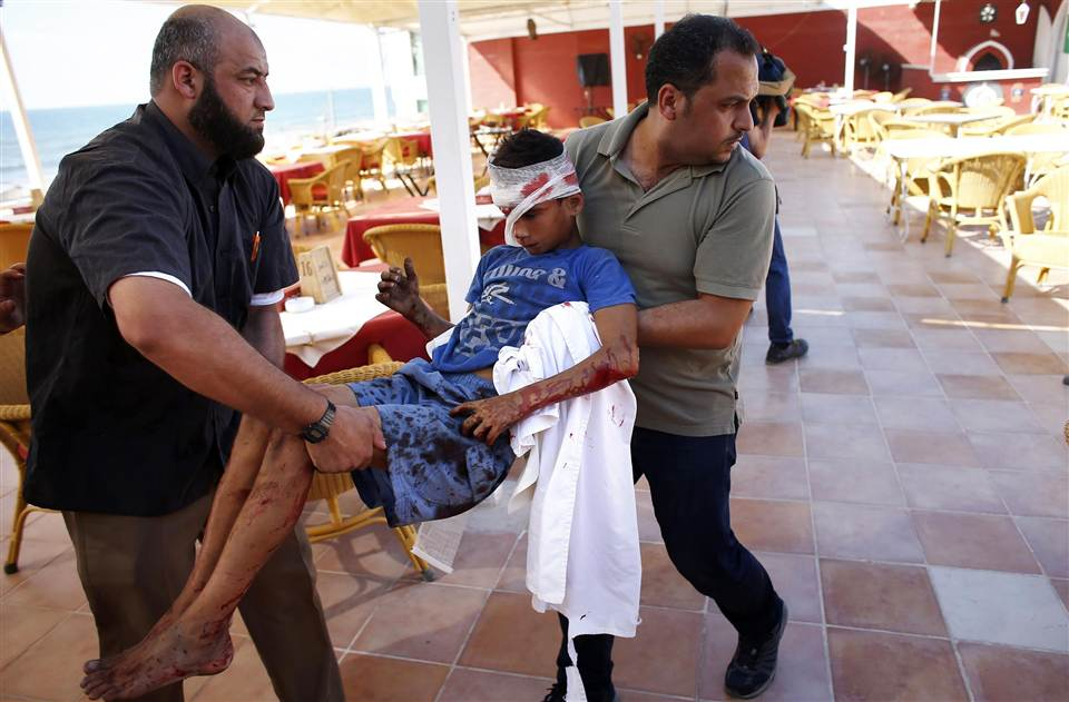 Employees and journalists carry a wounded boy into the hotel following an Israeli missile strike. Credit: Thomas Coex/AFP