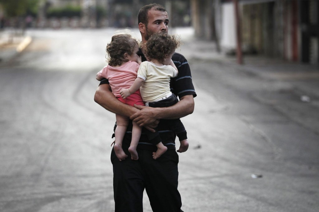 A Palestinian man carrying children flees the Shujayeh neighbourhood. REUTERS/Finbarr O'Reilly