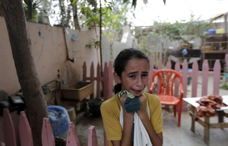 The sister of medic Fuad Jaber, who was killed while on duty in Gaza's eastern Shujayeh district, mourns during his funeral in Gaza City on July 20, 2014. (Photo: AFP - Mohammed Abed)