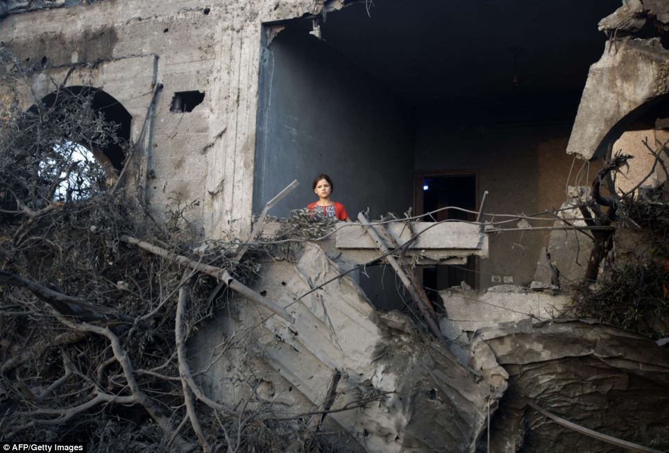 A young girl stands in her damaged home in Gaza following an air strike.