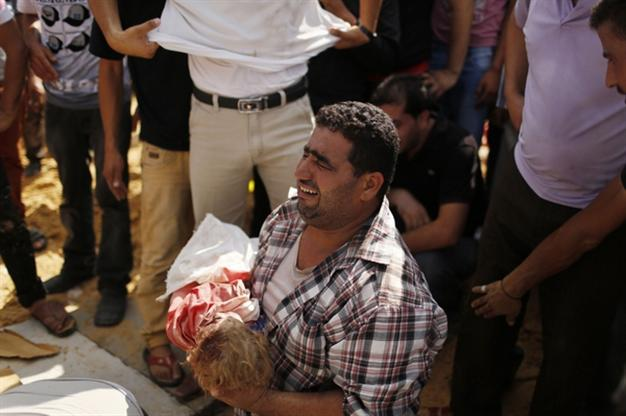 A relative cries as he carries the body of three-year-old Palestinian girl Haniyeh Abu Jarad, who medics said was killed along with her father and six other members from the same family by an Israeli tank shell, before her burial during their funeral in Beit Lahiya in the northern Gaza Strip July 19, 2014. REUTERS/Suhaib Salem