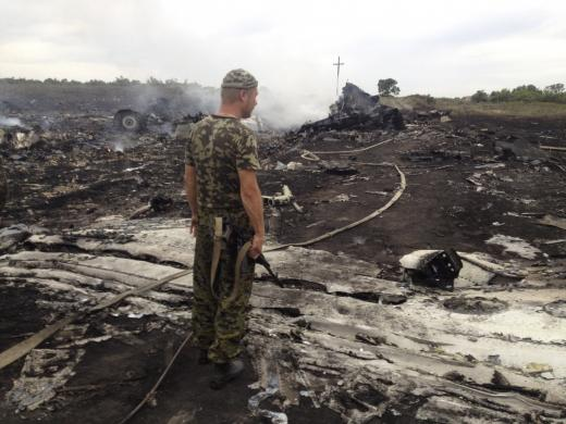 An armed pro-Russian separatist stands at the site of a Malaysia Airlines Boeing 777 plane crash in the settlement of Grabovo in the Donetsk region, July 17, 2014.  REUTERS/Maxim Zmeyev