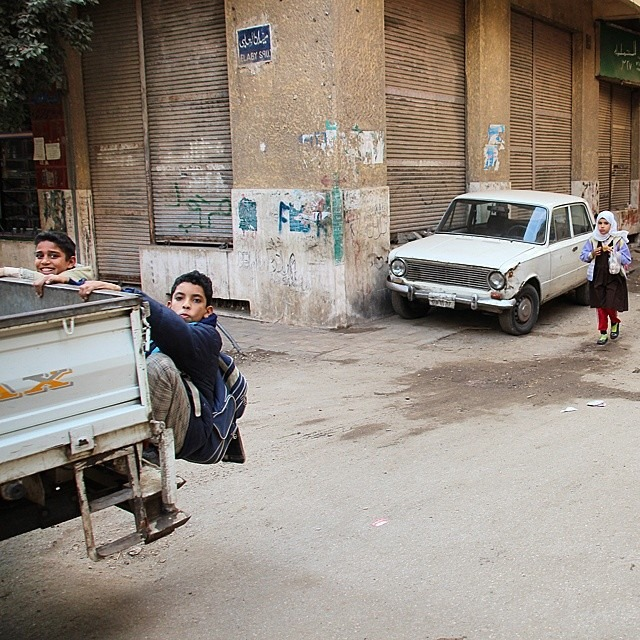 Boys catch a ride of the back of a pickup truck on their way home from school in the Haram district, Cairo. Photo by Shadi Rahimi