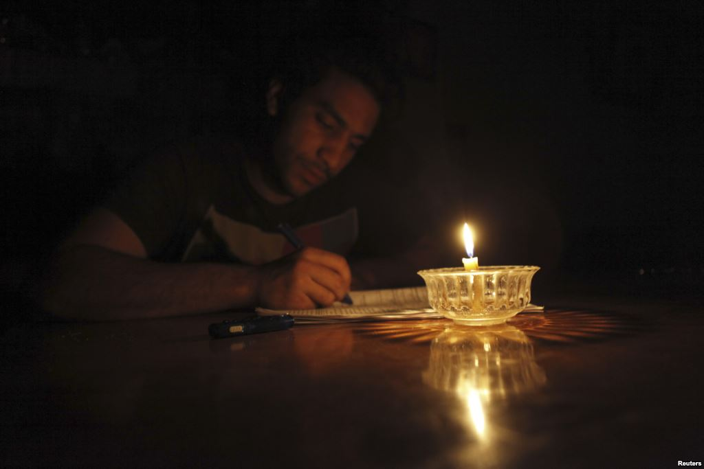 A student studies by candlelight during a power cut in May 2013. Credit: Reuters
