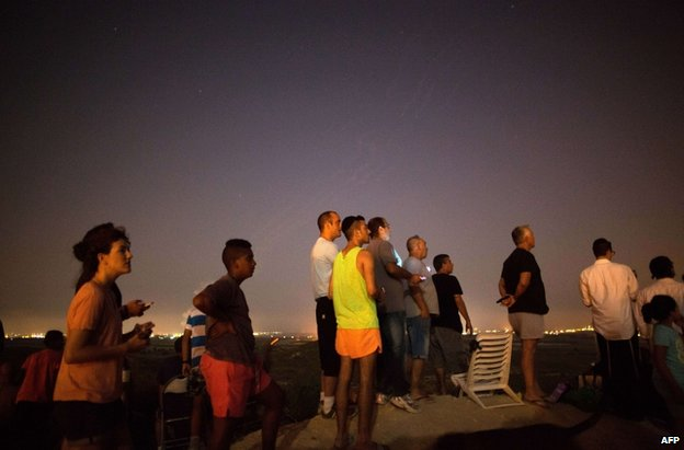 Israelis watching the bombardment of Gaza from near Sderot on Saturday evening Palestinians pass a damaged house after a Palestinian rocket hit Hebron in the West Bank, 12 July. Credit: AFP