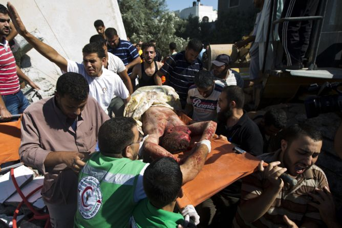 Emergency responders carry the body of a man, found under the rubble of his house following an Israeli airstrike on Maghazi refugee camp in central Gaza Strip on July 9, 2014. (MAHMUD HAMS/AFP/Getty Images)