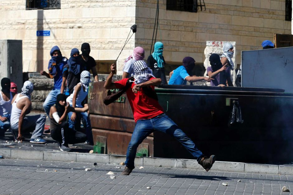 Masked Palestinian residents clash with Israeli police in Shuafat, a suburb of Jerusalem. Reuters: Baz Ratner