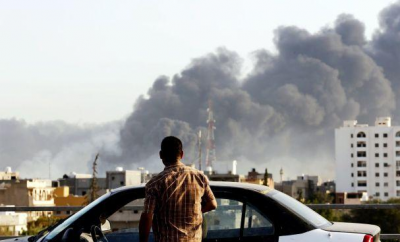 A man looks at smoke rising following an airstrike in Libya.