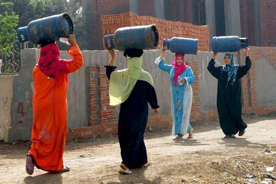 Women carrying empty gas cylinders, as Egypt's government said it lifted a subsidy on butane cooking gas. Photo: Reuters.