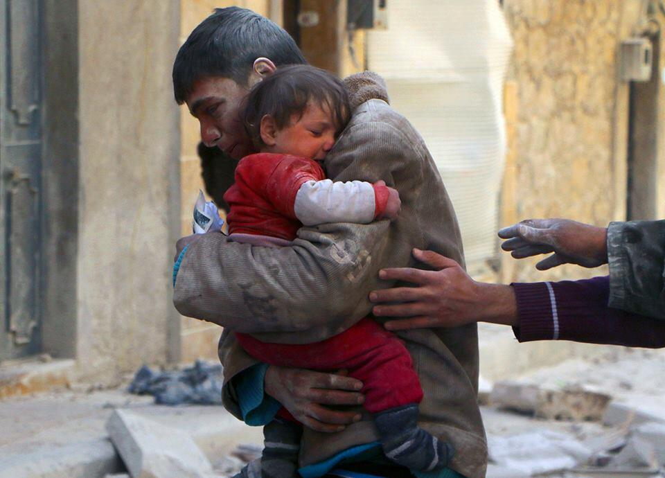 A boy rescues his sister from underneath the rubble of their home in Syria.
