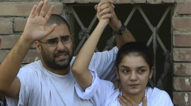 Surrounded by plainclothes policemen, Egyptian prominent blogger Alaa Abdel-Fattah, left, speaks to the crowd after attending, with his sister Sanaa, right, their father Ahmed Seif funeral in Cairo, Egypt, 28 August 2014. (Photo: AP)