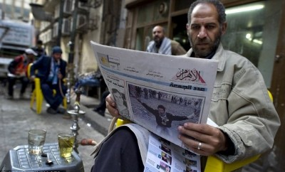 A man reads Egypt's state-owned Al-Ahram during the January 25 revolution.