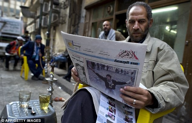 A man reads Egypt's state-owned Al-Ahram during the January 25 revolution. Credit: AFP