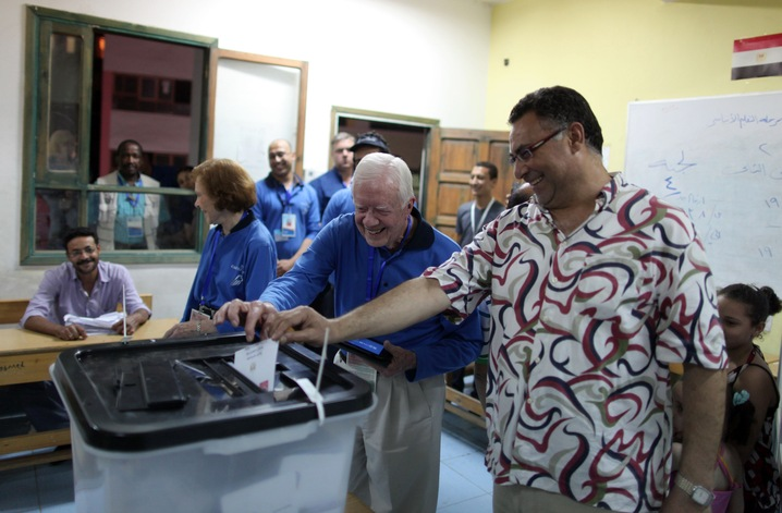 Former President Carter helps an Egyptian voter at a polling station in Cairo during the first round of presidential elections. in 2012. Photo by Wissam Saleh/AFP/Getty Images.