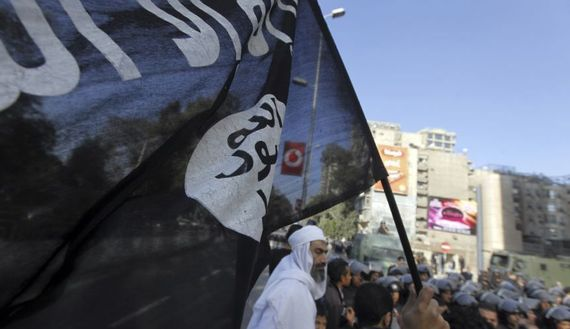 An Islamist protester holds a Salafist flag as Egyptian security forces stand guard during a protest against the French operation in Mali outside the French embassy in Cairo