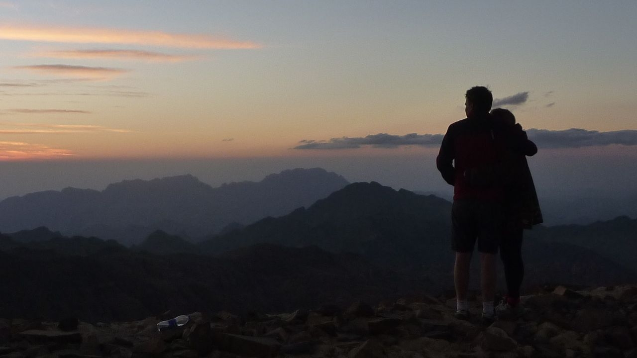 Two hikers, watching the sun go down from Jebel Abbas Basha