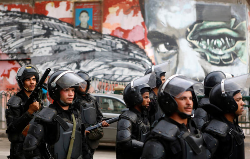 riot police walk in frong of graffiti depicting Bassem Mohsen along Mohamed Mahmoud during the third anniversary of the Mohamed Mahmoud Clashes. Credit: Reuters