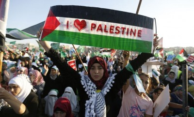A supporter of the Jordanian Muslim Brotherhood holds up a Palestinian flag during a rally in Amman