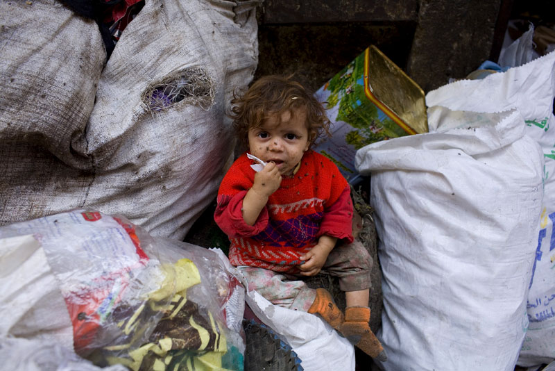 "A young child sits in a pile of trash on the streets of Moqqatam, a suburb of Cairo which is home to a people known as the Zabaleen, which means, plainly enough, ""the garbage collectors"".  Credit: Peter Dench"