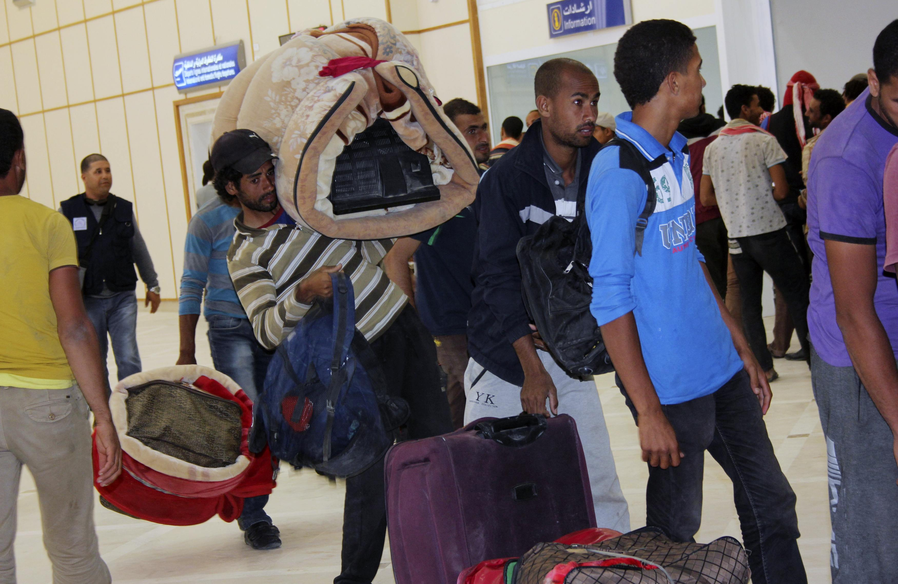 Egyptian men wait to board their plane to return home, at the Gabes Matmata airport, south of Tunisia
